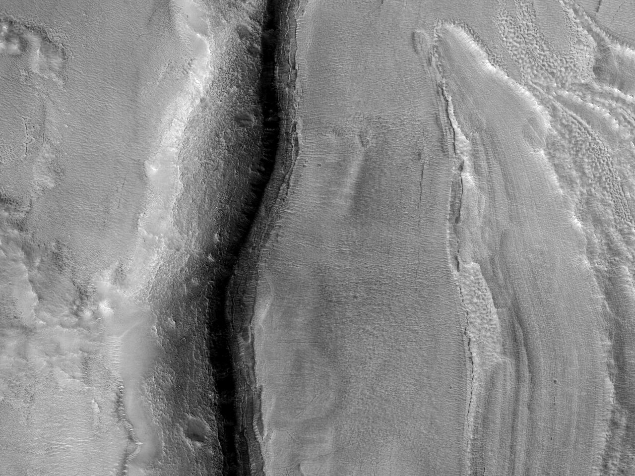 Marginea groasă a unui crater de impact în Protonilus Mensae