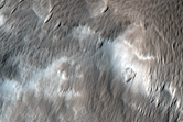 Uranius Tholus Stratigraphy Exposed in An Impact Crater