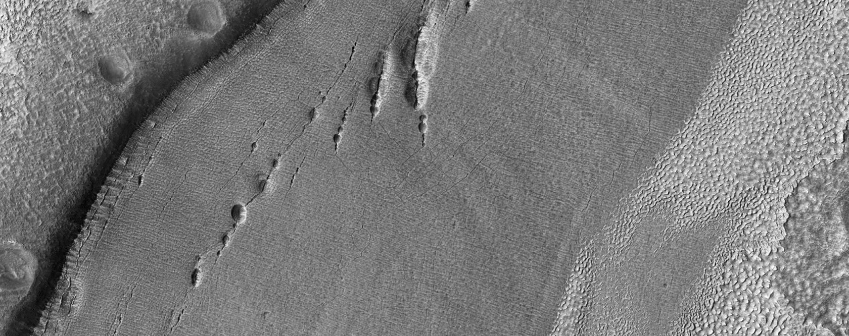 Pits along Fractures in Crater Floor Material