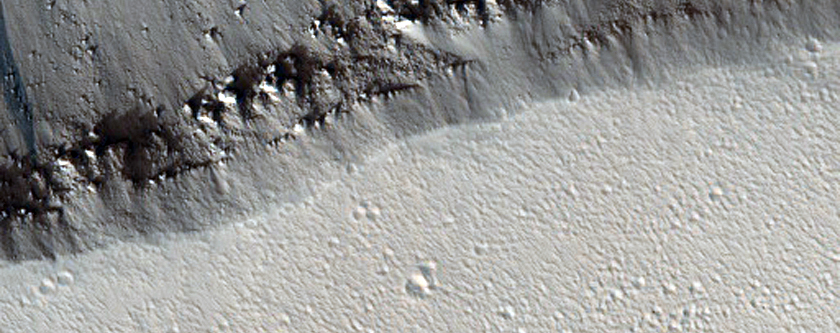Slope Streaks Diverted around Crater in Trough Wall