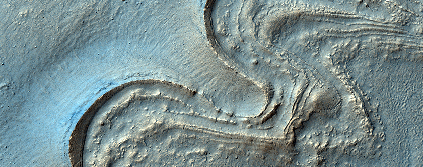 Gullies and Curved Ridges at the Base of Crater Walls