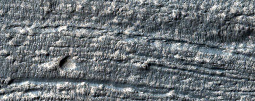 Debris Apron Material Between Crater Rim and Massif in Promethei Terra