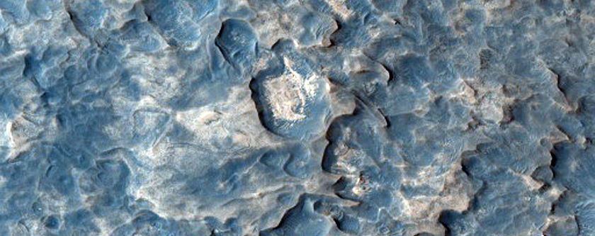 Terreno muy irregular en contacto con llanuras rojizas al norte de Meridiani