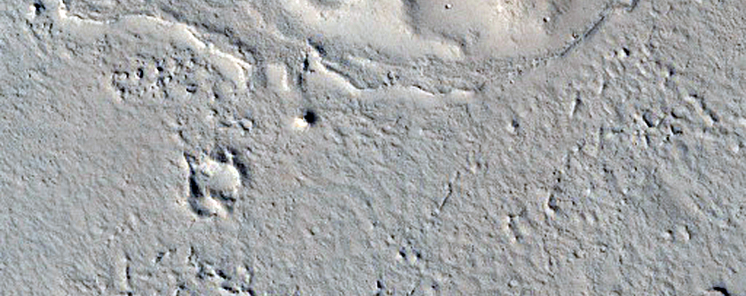 Terraced Hills Associated with Flow Features in Tartarus Colles