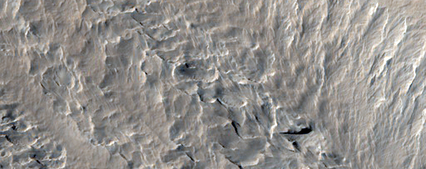 Pitted and Layered Materials in Olympus Mons Aureole