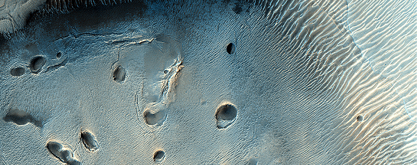A Dark-Toned, Pitted Mound in a Crater in Northeast Arabia Terra