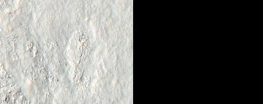 Wall and Ejecta of Well-Preserved Crater in Aonia Terra