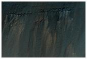 Materia stratificata sotto un cratere da impatto sulla parete di Coprates Chasma