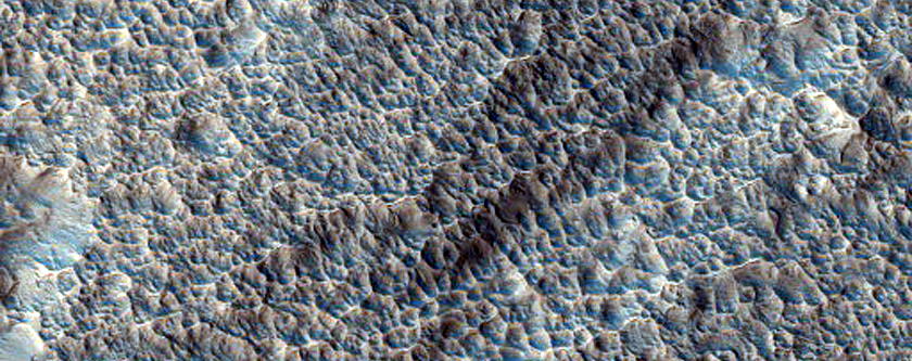 Heavily Pitted Distal Rampart Ejecta of Mojave Crater